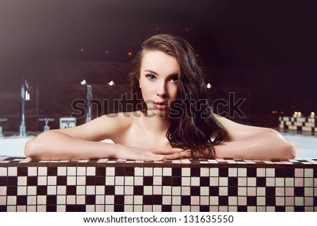 Young woman taking bath with candles in back - stock photo