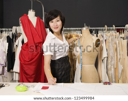 Young woman taking down measurements - stock photo