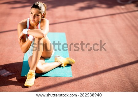 Young woman taking exercise outdoors - stock photo