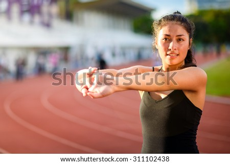 Young woman taking exercise outdoors on running track