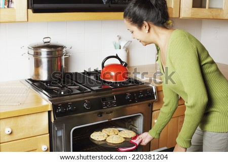 Young woman taking food out of the oven - stock photo