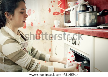 Young woman taking hot frying pan out from oven