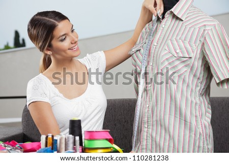 Young woman taking measurement of a shirt with dressmaking accessories in foreground - stock photo