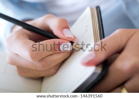 young woman taking notes at home