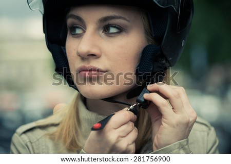 Young woman taking on/off her helmet - stock photo