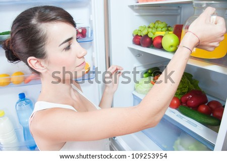 young woman taking orange juice out of fridge - stock photo
