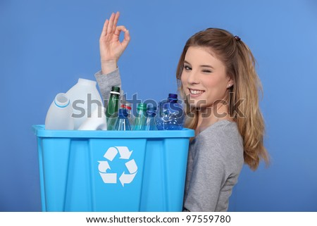 Young woman taking out the recycling - stock photo