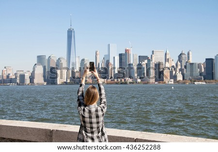 Young woman taking photo at New York City skyscrapers, USA - stock photo