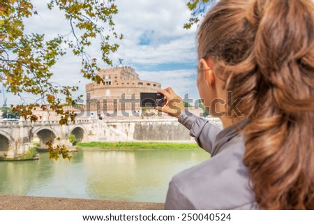 Young woman taking photo of castel sant'angelo in rome italy. rear view - stock photo