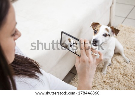 Young woman taking photo of her dog - stock photo