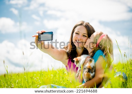Young woman taking photo with her smart-phone camera of herself, her daughter and kitten - stock photo