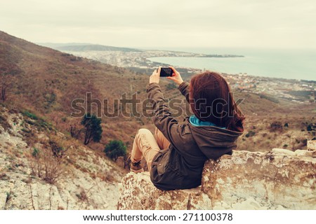 Young woman taking photographs beautiful landscape with mobile phone - stock photo