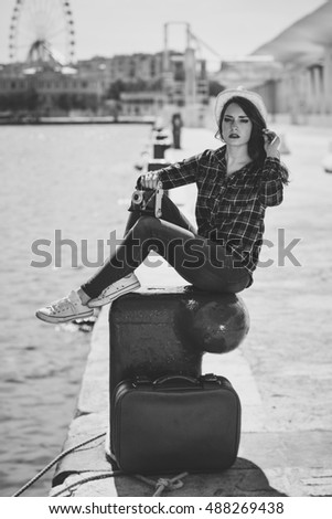 Young woman taking photographs with a vintage camera sitting in a harbor. Girl wearing plaid shirt, blue jeans and sun hat. Black and white photograph.