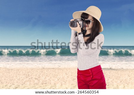 Young woman taking pictures at beach. shot on summertime - stock photo