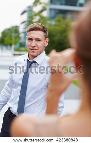 Young woman taking pictures of business man with smartphone in the city - stock photo