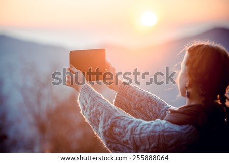Young woman taking pictures on a tablet in mountains at sunset. Toned picture - stock photo