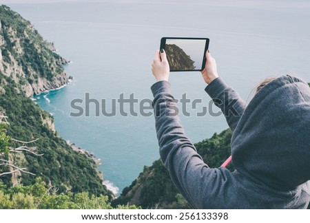 Young woman taking pictures on a tablet in mountains. Toned picture - stock photo