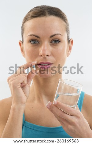 Young woman taking pill