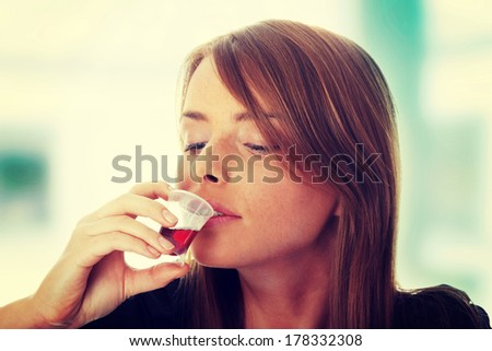Young woman taking pills and syrup, isolated on white - stock photo
