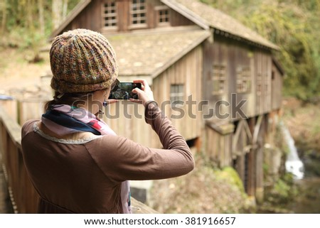 Young woman taking scenic photos with a cellphone.