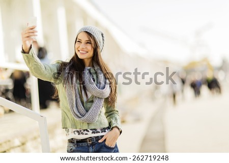 Young woman taking selfie on the street - stock photo