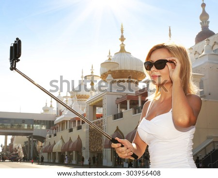 Young woman taking selfie photo with stick in front of Taj Mahal Casino, Atlantic City