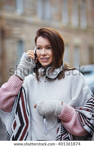 Young woman talk over her mobile while walking down the street - stock photo