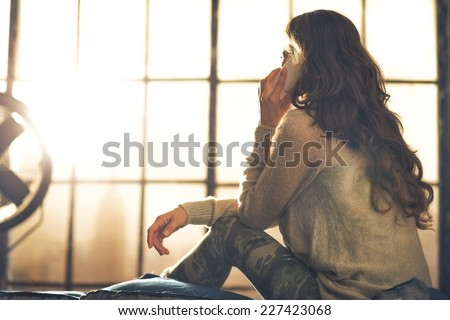 Young woman talking cell phone in loft apartment. rear view - stock photo