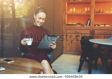 Young woman talking in video chat with her sister via digital tablet while sitting in her favorite cafe and drink delicious green tea, female watching movie on touch pad while breakfast in coffee shop - stock photo