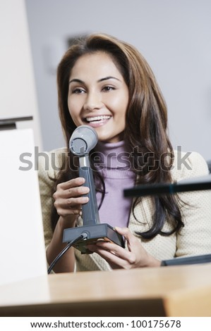 Young woman talking into a microphone - stock photo
