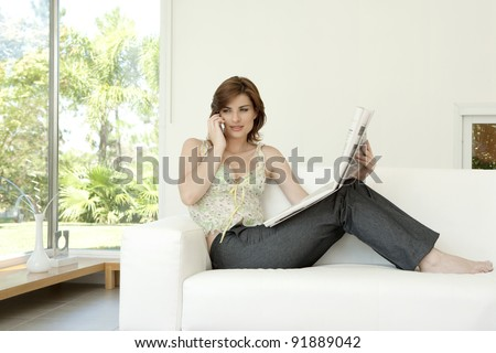 Young woman talking on a cell phone while reading a newspaper at home.