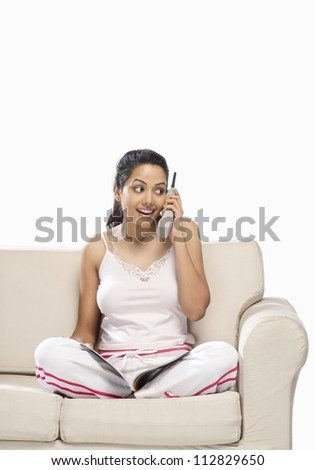 Young woman talking on a cordless phone and holding a magazine - stock photo