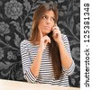Young Woman Talking On Cellphone against a floral pattern background - stock