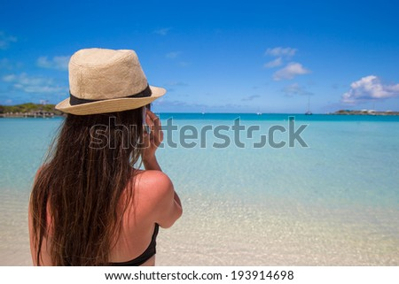Young woman talking on her phone at tropical beach - stock photo
