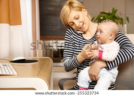 Young woman talking on mobile holding baby on lap. - stock photo