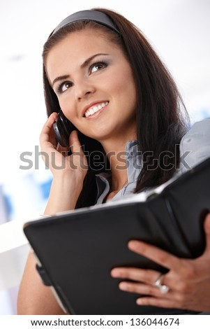 Young woman talking on mobile, holding organizer, smiling. - stock photo