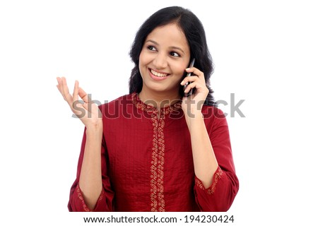 Young woman talking on mobile phone against white background - stock photo