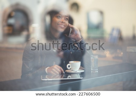 Young woman talking on phone in coffee shop - stock photo