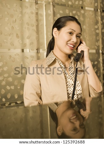 Young woman talking on phone sitting at a table