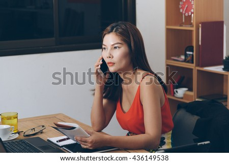 young woman talking on the mobile phone and smiling while sitting at her working place in office