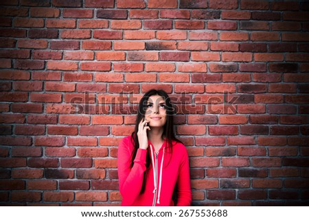 Young woman talking on the phone and looking up at copyspace over brock wall. Wearing sports jacket - stock photo