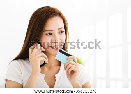 young woman talking on the phone and showing  credit card