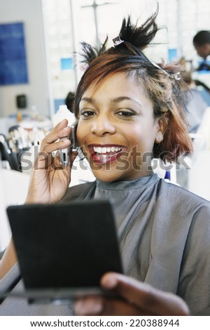 Young woman talking on the phone at the hairdressers - stock photo