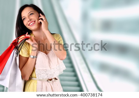 Young woman talking on the phone at the mall - stock photo