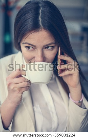 Young woman talking on the phone. Drinking coffee.