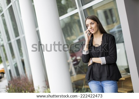 Young woman talking on the phone in front of office