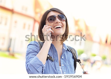 Young woman talking on the phone in the city - stock photo