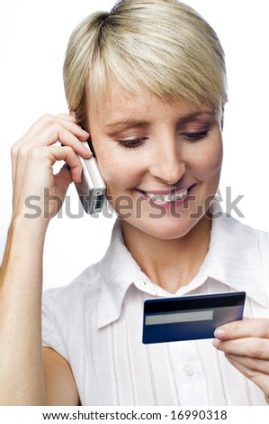 young woman talking on the phone looking on credit card