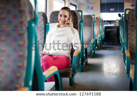 Young woman talking on the phone on the train - stock photo