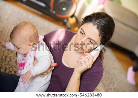 Young woman talking on the phone while holding a baby girl in her arms.